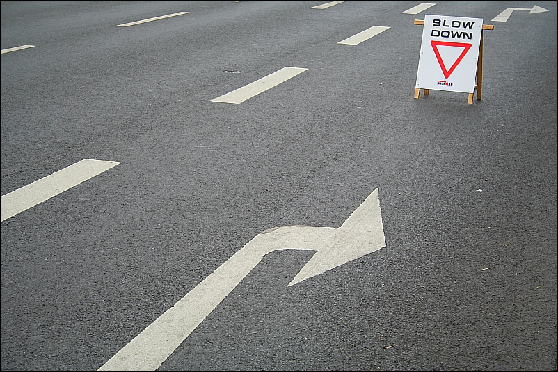 a road with a sign board showing 'Slow'