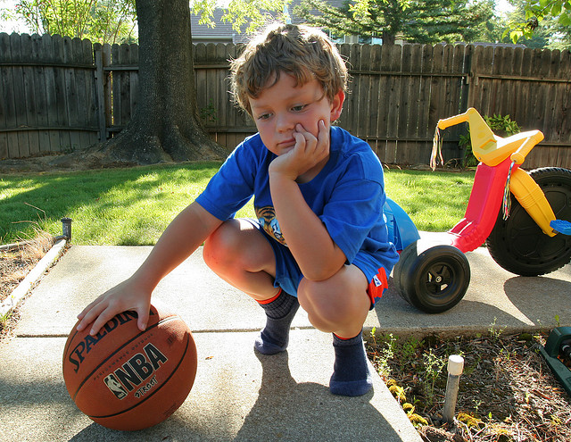 bored kid holding a ball