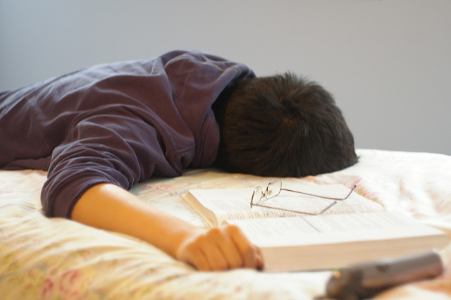 a student sleeping on the bed while studying